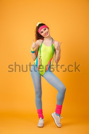 Sad astonished sportswoman standing and measuring her waist with tape Stock photo © deandrobot