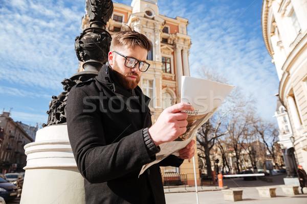 Yandan görünüş yakışıklı sakallı adam kat gazete Stok fotoğraf © deandrobot