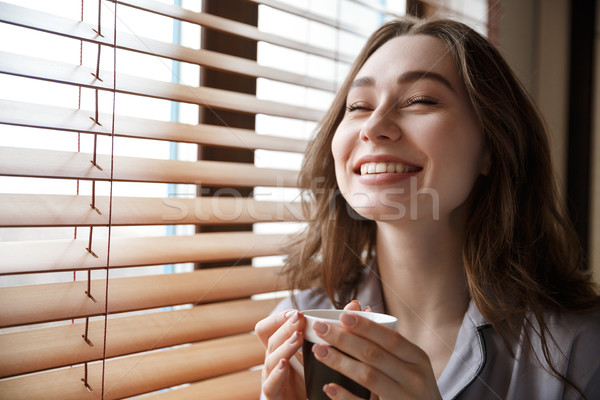 Close up portrait of laughing woman near the window Stock photo © deandrobot