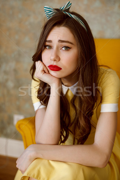 Vertical image of sad woman on armchair Stock photo © deandrobot