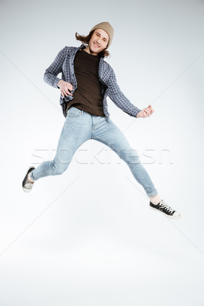 Vertical image of Smiling hipster playing on imaginary guitar Stock photo © deandrobot