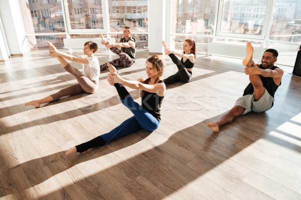 Cheerful young people stretching legs and doing yoga in studio Stock photo © deandrobot