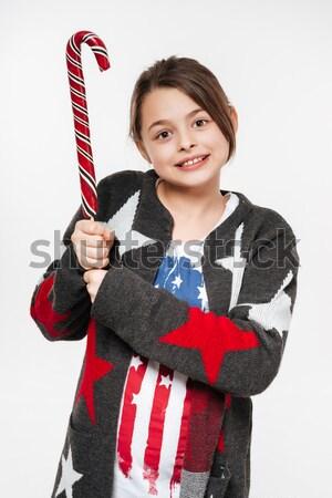 Lächelnd junge Mädchen halten candy Hand Kleidung Stock foto © deandrobot