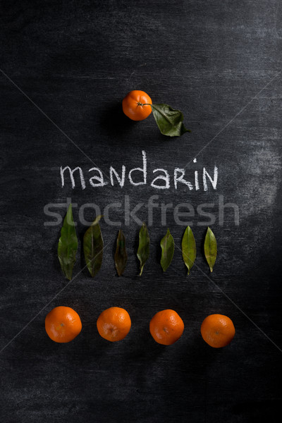 Tangerines over dark chalkboard background Stock photo © deandrobot