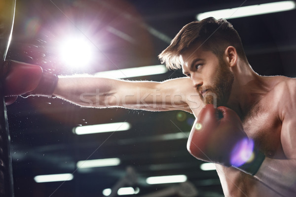 Emotional young strong sports man boxer make exercises Stock photo © deandrobot