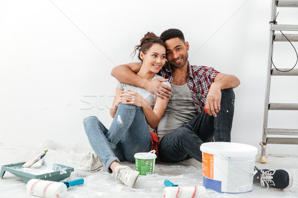 Happy multiethnic young couple renovating home and hugging Stock photo © deandrobot