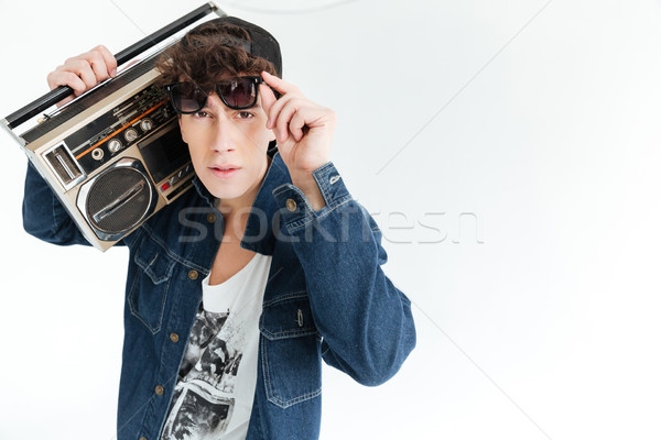 Handsome young man holding boombox. Looking at camera. Stock photo © deandrobot