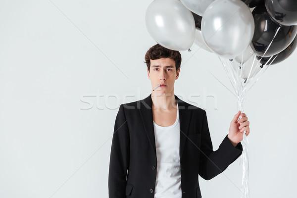 Higgadt férfi tart levegő léggömbök dohányzás Stock fotó © deandrobot