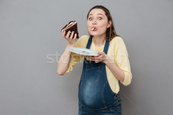 Portrait of a hungry pregnant woman eating sweet chocolate cake Stock photo © deandrobot
