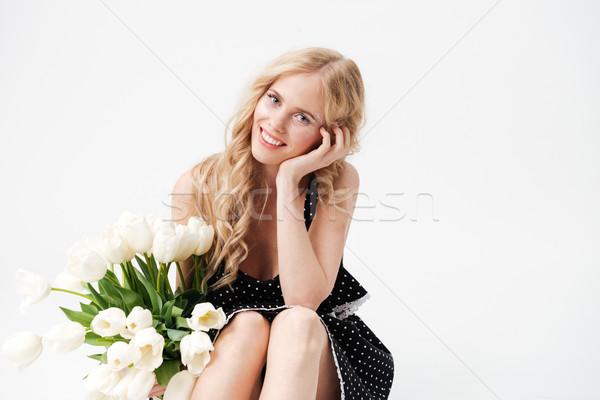 Mosolyog szőke nő ül padló virágcsokor virágok Stock fotó © deandrobot