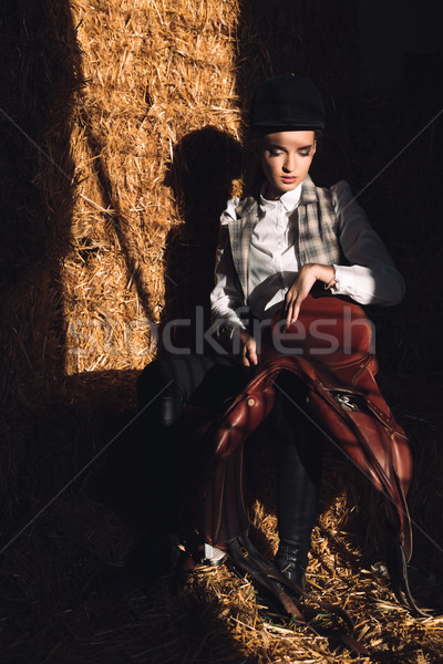 Serious young girl sitting in barn with seddle Stock photo © deandrobot
