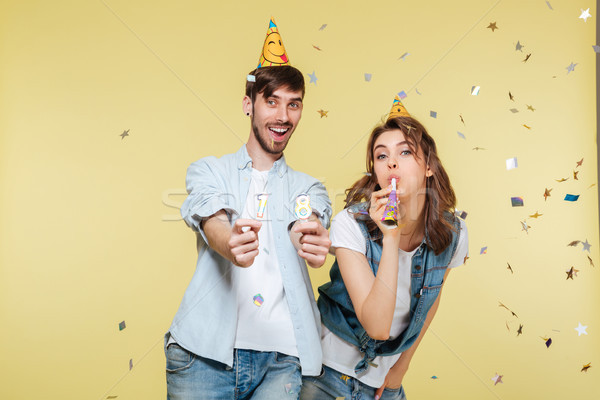Happy brother and sister standing over yellow background Stock photo © deandrobot