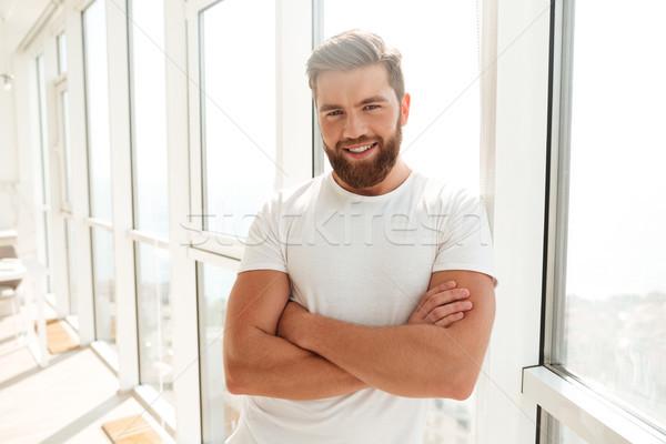 Glimlachend bebaarde man permanente armen venster Stockfoto © deandrobot