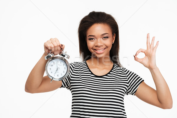 Afro american woman holding alarm clock and showing ok gesture Stock photo © deandrobot