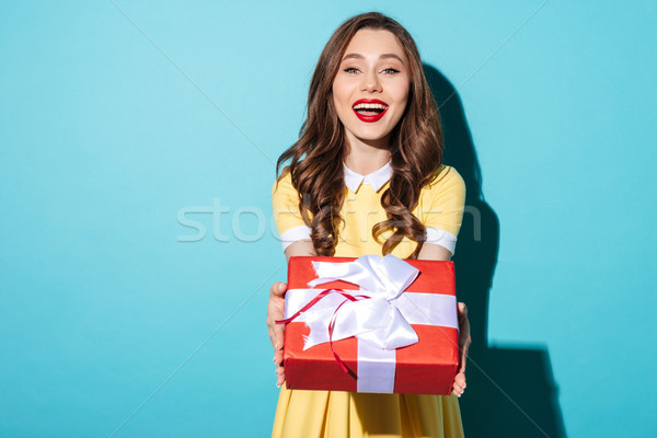 Cheerful pretty girl in dress giving present box to camera Stock photo © deandrobot