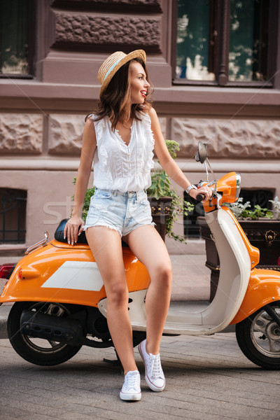 Happy young woman outdoors standing near scooter Stock photo © deandrobot