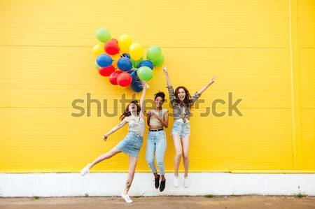Smiling women friends have fun with shopping trolley and balloons. Stock photo © deandrobot