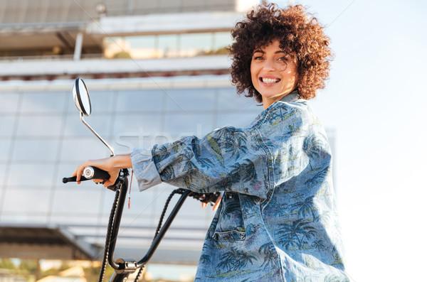 Сток-фото: молодые · улыбающаяся · женщина · сидят · современных · мотоцикле · улице