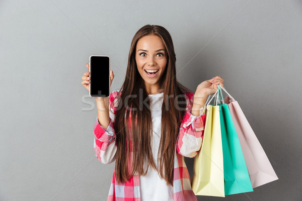 Photo of amazed young brunette holding shopping bags, showing bl Stock photo © deandrobot