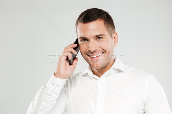 Smiling young man talking by phone. Stock photo © deandrobot