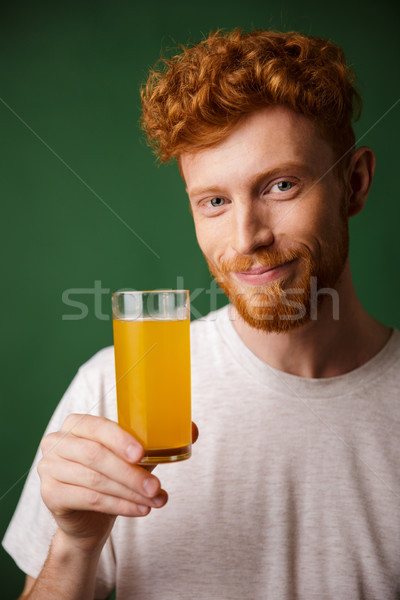 Portrait of handsome smiling bearded man holding glass of orange Stock photo © deandrobot