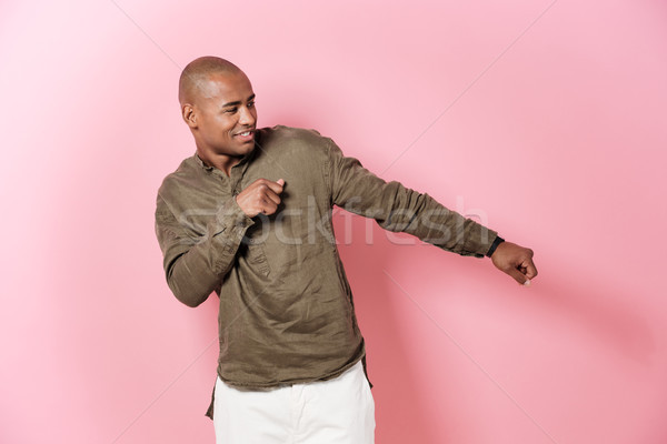 Carefree african man dancing in studio and looking away Stock photo © deandrobot