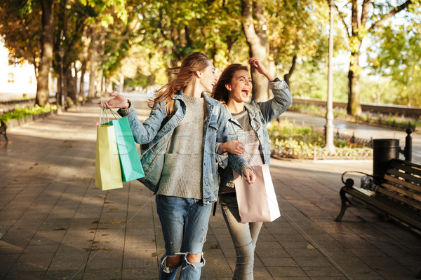Photo of two beautiful woman friends holding shopping bags while Stock photo © deandrobot