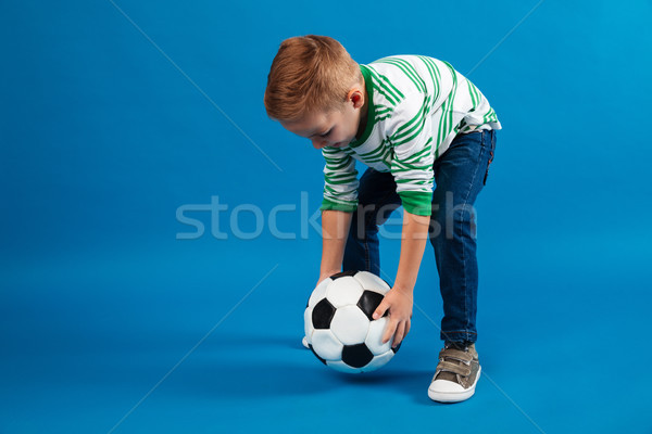 Portrait of a kid going to kick a soccer ball Stock photo © deandrobot