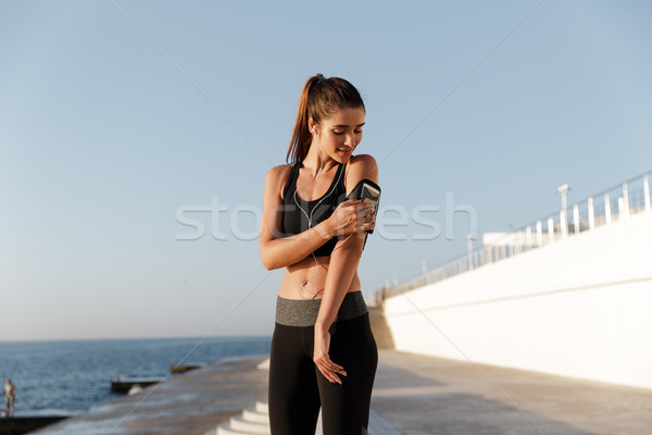 Stock photo: Smiling young sports woman listening music using mobile phone.