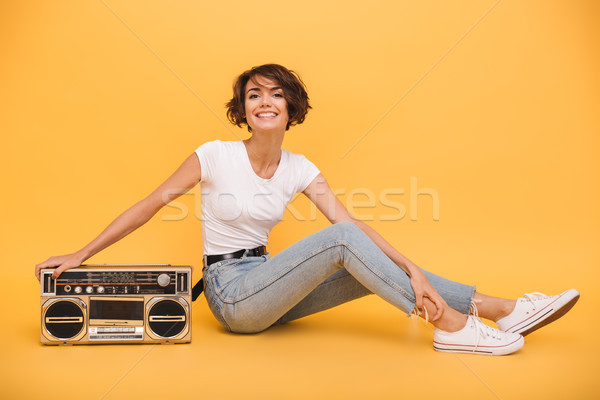 Portrait of a pretty joyful girl sitting with record player Stock photo © deandrobot
