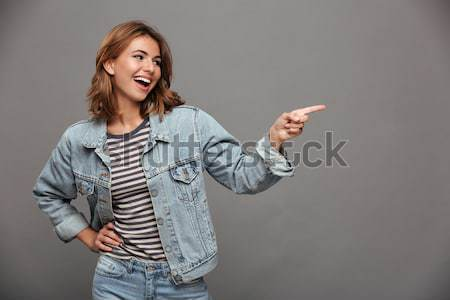 Overjoyed teen girl in jeans jacket pointing with finger, lookin Stock photo © deandrobot