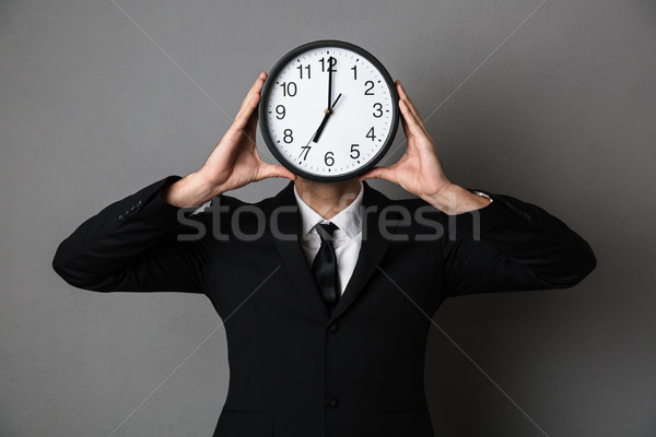 Young man in black suit holding clock in front of his face Stock photo © deandrobot