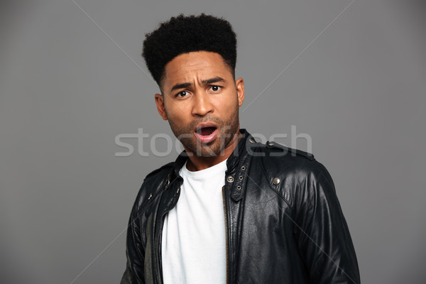 Portrait of a surprised shocked african man in leather jacket Stock photo © deandrobot