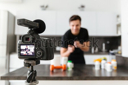 Close up of a video camera filming smiling male blogger Stock photo © deandrobot