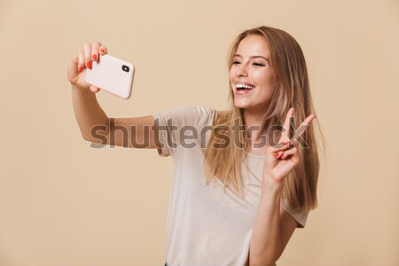Contented smiling woman with red lips typing text message or scr Stock photo © deandrobot