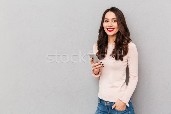 Horizontal photo of smiling woman with red lips typing text mess Stock photo © deandrobot