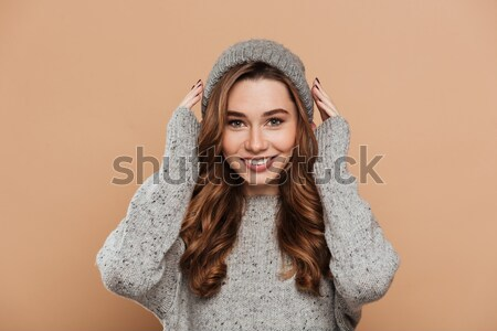 Young tender brunette girl in gray knitted sweater and earmuffs  Stock photo © deandrobot
