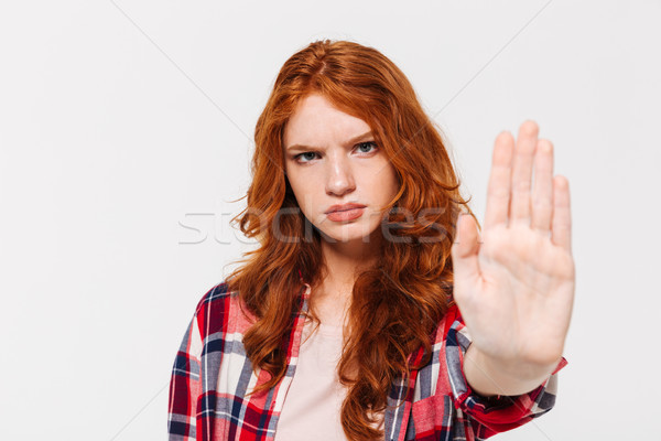 Serious ginger woman in shirt showing stop gesture at camera Stock photo © deandrobot