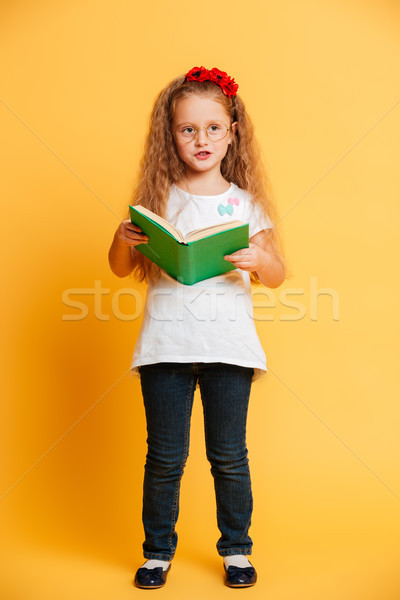 Cute pretty girl wearing glasses looking aside reading book. Stock photo © deandrobot