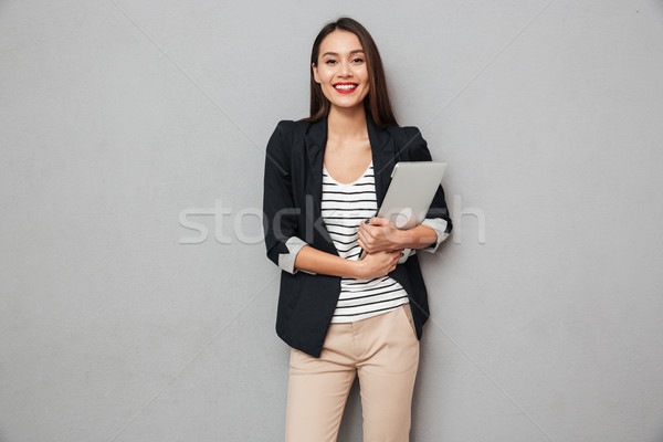 Pleased business woman holding laptop computer and looking at camera Stock photo © deandrobot