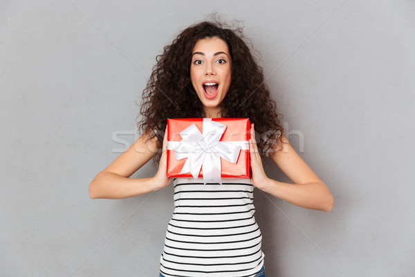 Pleased female 20s holding red box gift-wrapped being excited an Stock photo © deandrobot