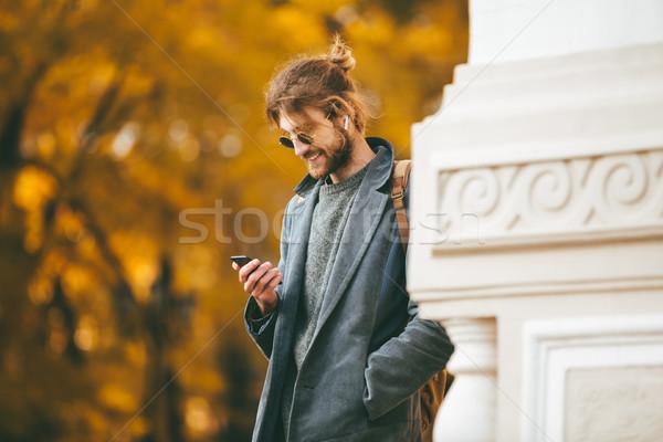 Portrait of a stylish bearded man in earphones Stock photo © deandrobot