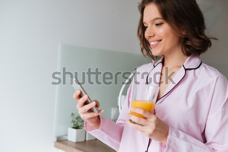 Portrait of a happy young woman in pajamas Stock photo © deandrobot