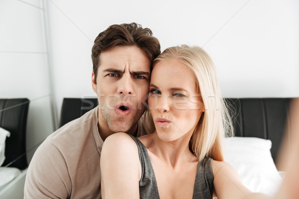 Funny attractive lovers making selfie and grimacing in the morning Stock photo © deandrobot