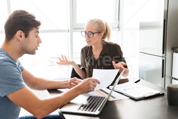Young lady has a quarrel with her man while working with papers Stock photo © deandrobot