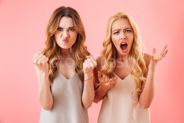 Two angry displeased pretty women in pajamas looking at camera Stock photo © deandrobot