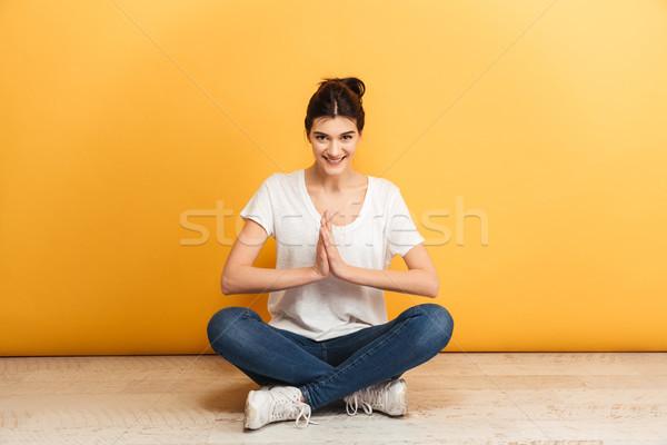 Portré mosolyog fiatal nő ül lábak keresztbe padló Stock fotó © deandrobot