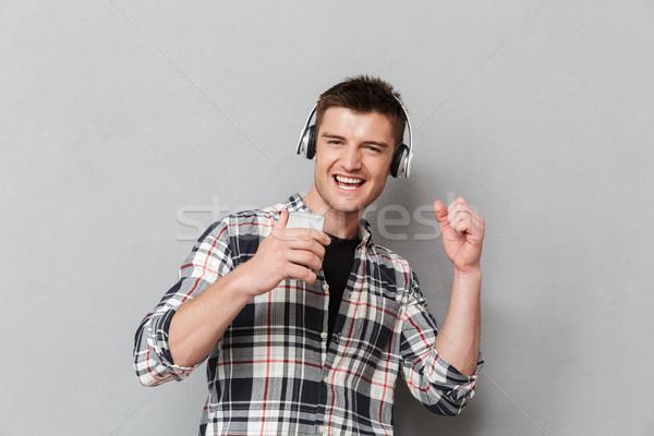 Portrait heureux jeune homme écouter de la musique casque Photo stock © deandrobot