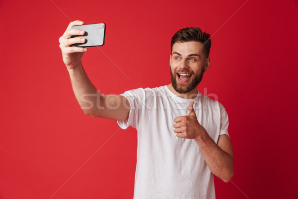 Happy young man make selfie by mobile phone make thumbs up gesture. Stock photo © deandrobot