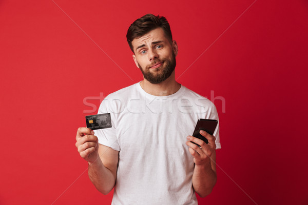 Foto stock: Nervioso · joven · teléfono · móvil · tarjeta · de · crédito · mirando
